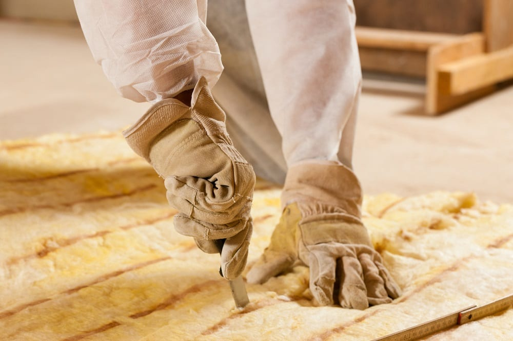 Man cutting some glass wool as material for thermal insulation of a new building